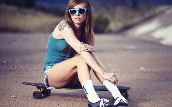 Девушка сидящая на скейте