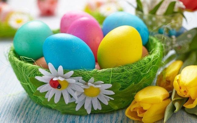 Разноцветные пасхальные яйца в корзине