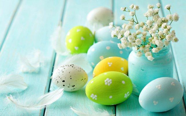 Пасхальные яйца рядом с белыми цветами в голубой банке