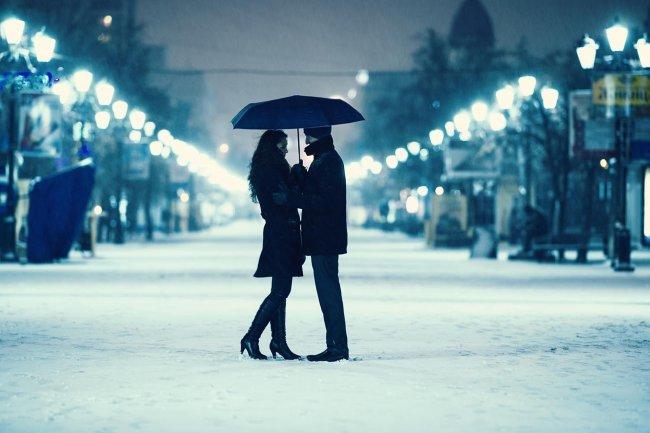 Девушка с мужчиной под черным зонтом