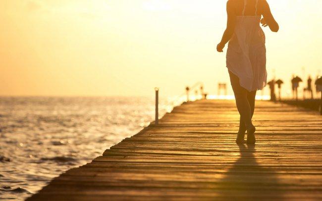 Девушка на пирсе на фоне захода солнца