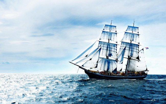 Корабль с белыми парусами в море