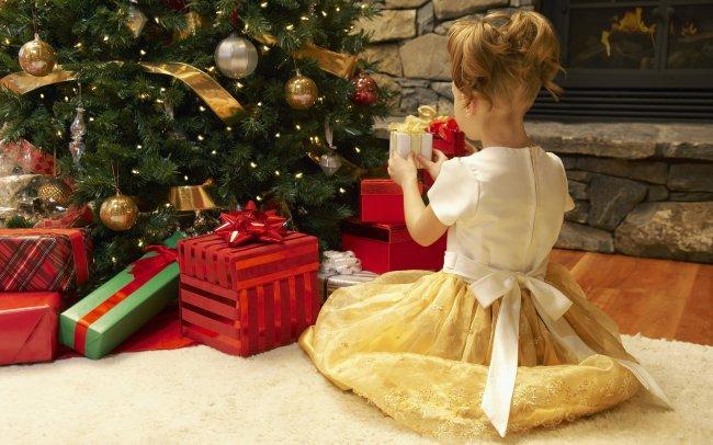 Девочка и новогодние подарки под елкой