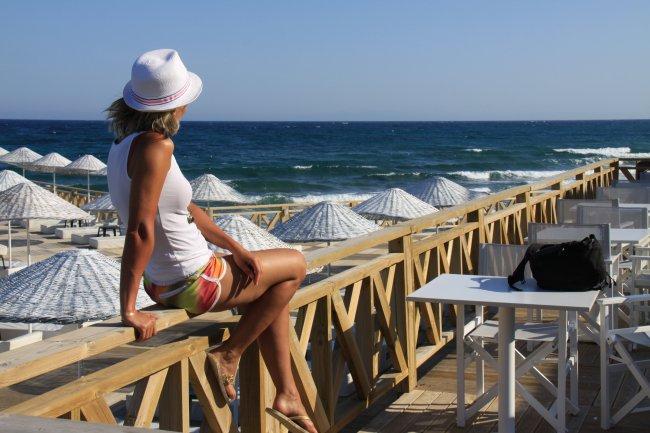 Девушка в шляпе сидит на перилах с видом на море