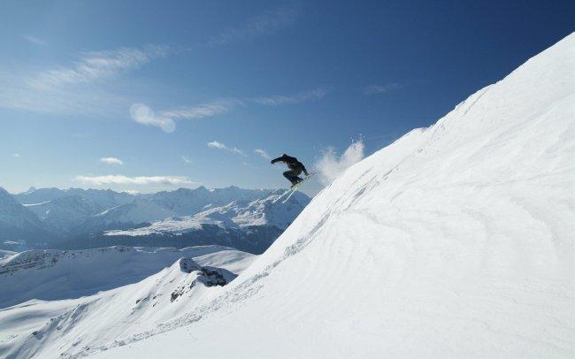Горнолыжник спускается со снежной горы