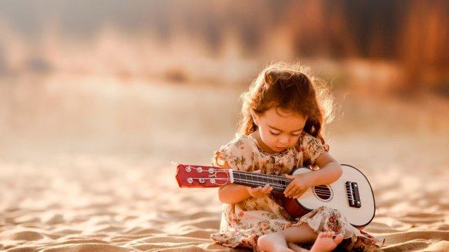 Маленькая девочка играет на гитаре