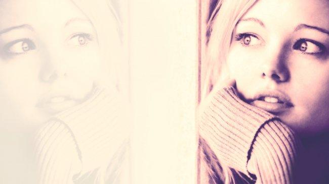 Лицо девушки отражается в оконном стекле