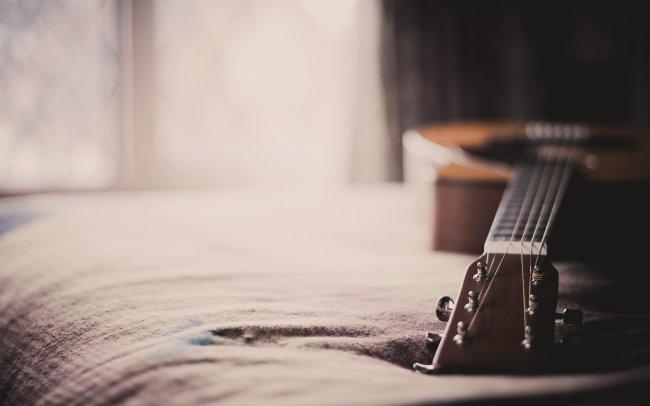 Акустическая гитара на кровати
