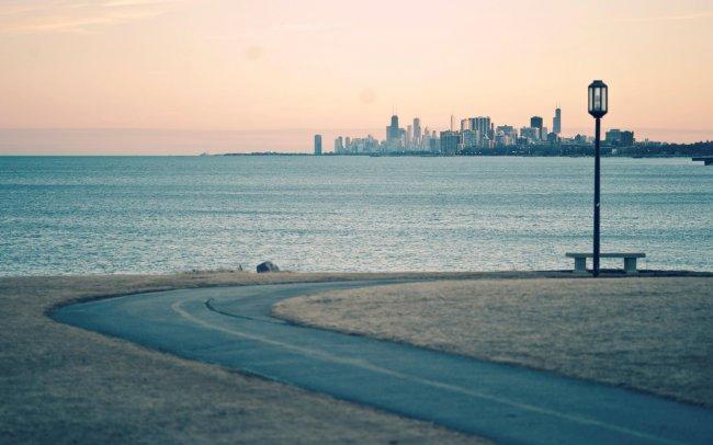 Дорога с лавочкой у моря с видом на город