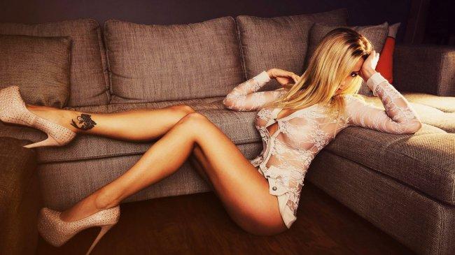 Девушка с татуировкой на лодыжке, возле дивана
