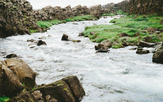 Река с быстрым течением, текущая среди каменистых берегов