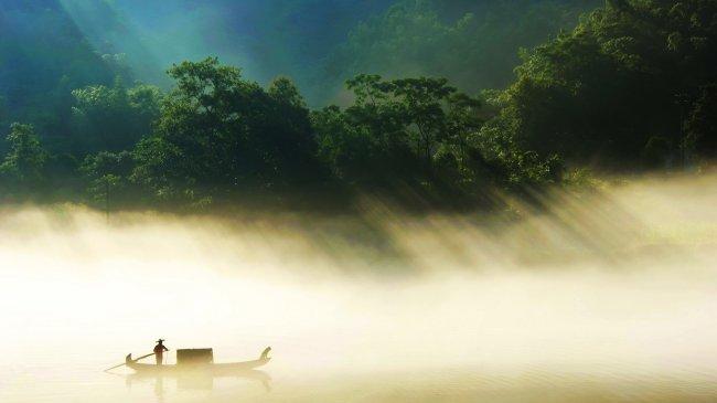 Человек и собака плывущие в лодке по туманной реке