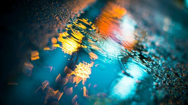 Капли дождя падают в лужу на асфальте