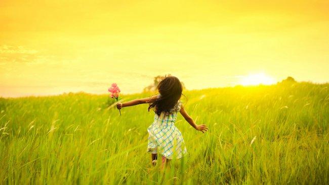 Девочка бежит по лугу с цветами