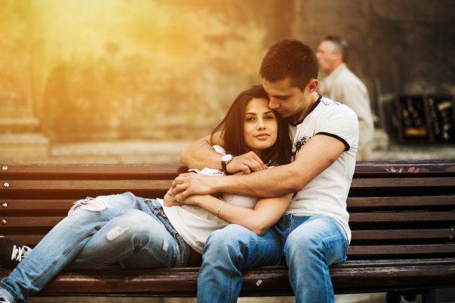 Влюбленная пара сидит на скамейке в парке обнявшись