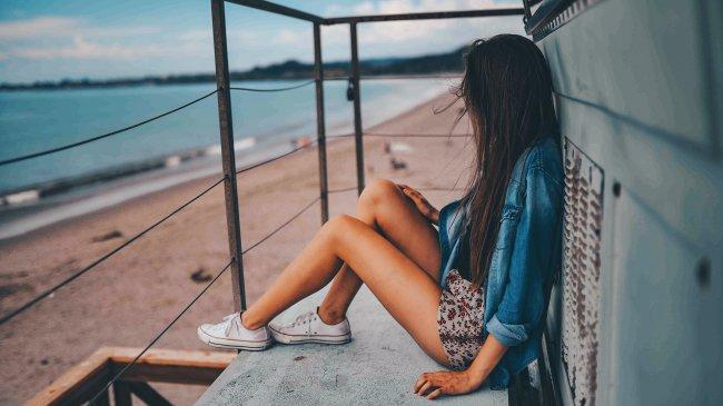 Девушка сидит возле моря