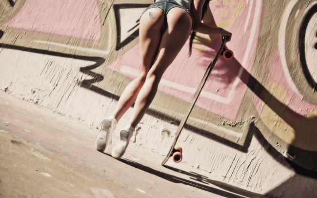Девушка со скейтбордом возле граффити стены