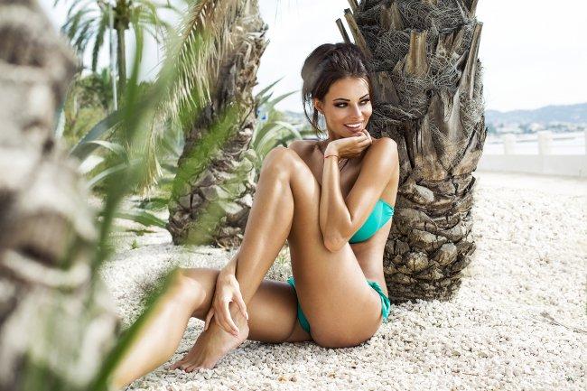 Красивая улыбающаяся девушка под пальмой на пляже