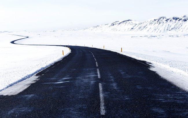 Извилистая дорога среди снега и заснеженных холмов