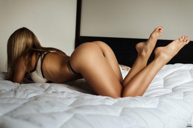 Девушка с красивой фигурой позирует на кровати