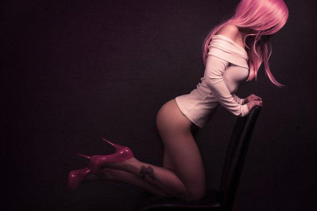 Девушка с розовыми волосами облокотившись на спинку стула