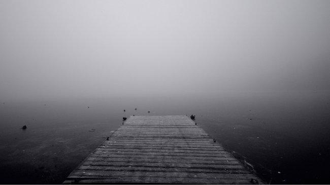Деревянный пирс, уходящий в туманное озеро