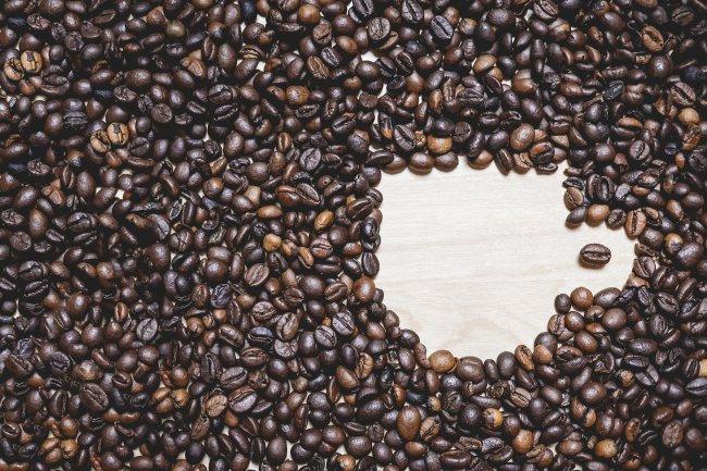 Кофе в зернах размещены в форме чашки кофе