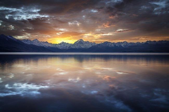 Горное озеро на фоне снежных гор