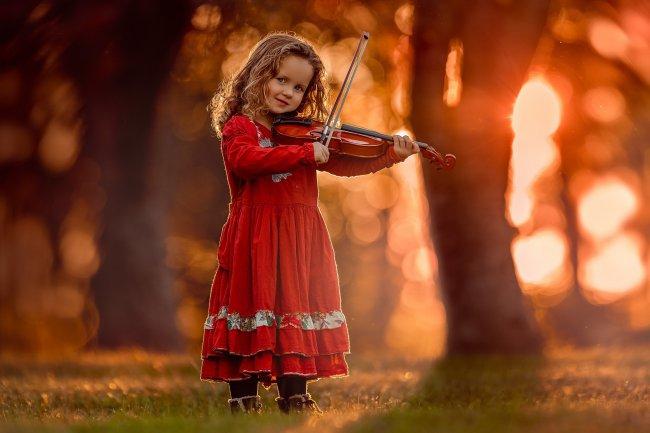 Девочка в красном платье играет на скрипке