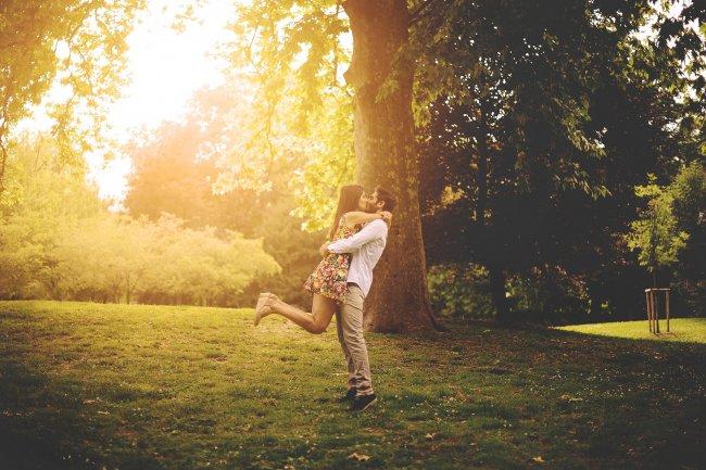Девушка радостно целуется в парке с парнем