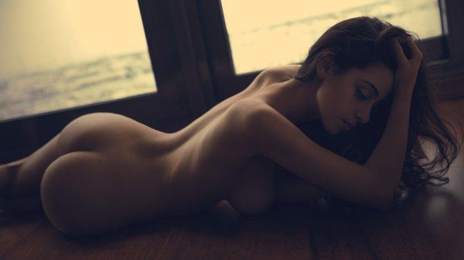 Обнаженная девушка на полу у окна