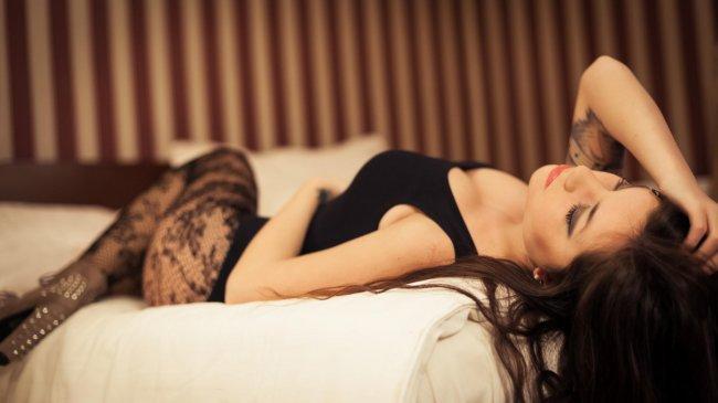 Брюнетка в боди лежа на кровати