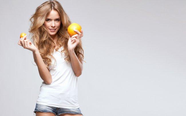 Девушка держит в руках апельсины