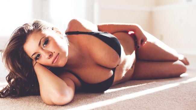 Девушка с красивой фигурой лежит на полу