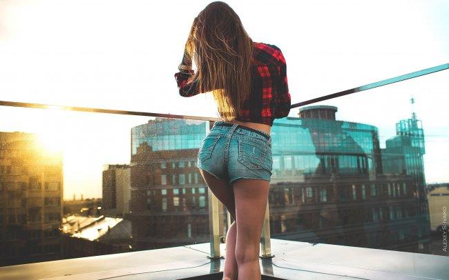 Девушка на крыше здания на рассвете