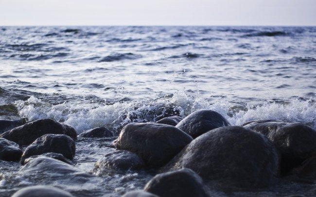 Морская волна омывает камни на берегу