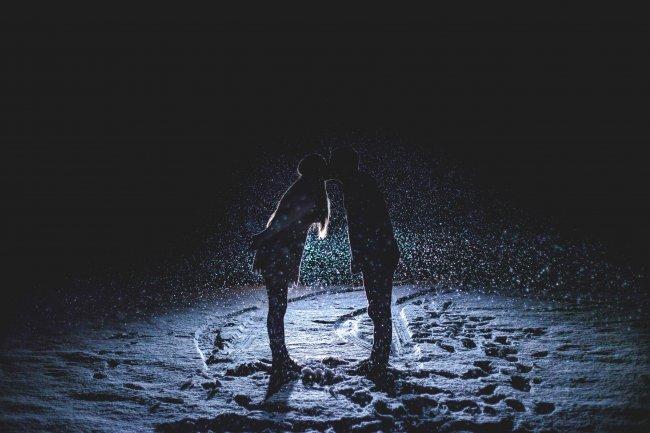 Целующиеся парень и девушка, стоящие под падающим снегом