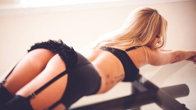 Блондинка позирует на стеклянном столе
