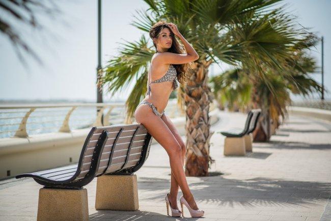 Красивая девушка позирует рядом с пальмой