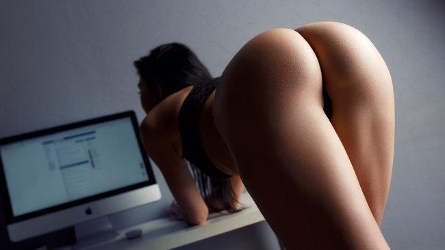 Девушка позирует у компьютера
