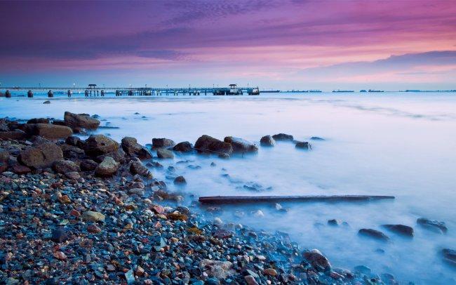 Морской берег на закате с видом на пирс
