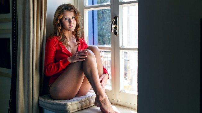 Рыжая девушка в красной кофточке у окна
