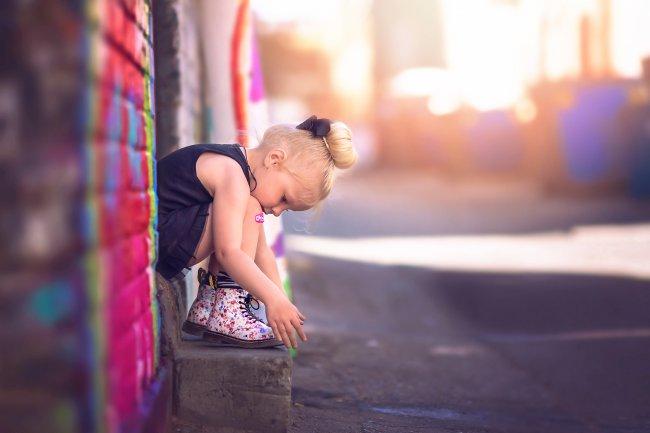 Маленькая девочка сидит на лестнице