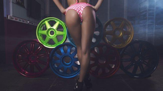 Шикарные женские ножки на фоне автомобильных дисков