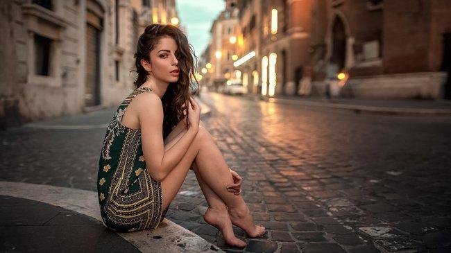 Девушка сидит на бордюре