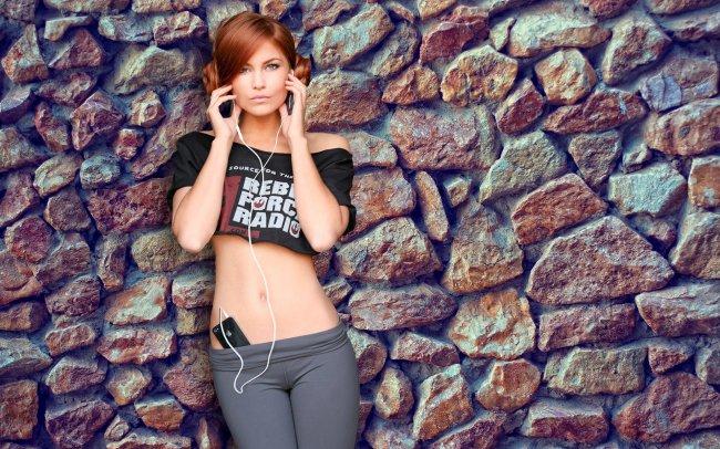 Девушка на фоне каменной стены в наушниках