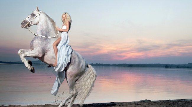 Красивая блондинка в длинном платье верхом на коне