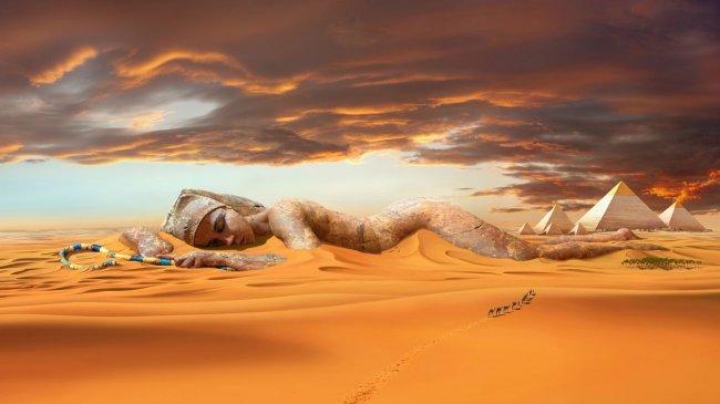 Клеопатра лежит на песке рядом с пирамидами