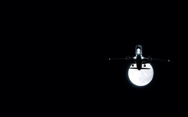 Самолет на фоне ночной луны