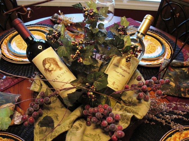 Две бутылки итальянского вина и виноград на сервированном столе